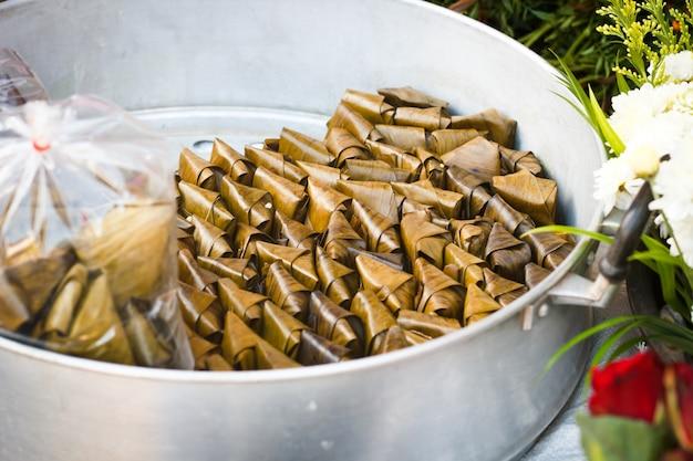 Tajlandzki tradycyjny kleisty ryżowy deser w bananowym liściu pakuje bubel w tajlandia rynku. khow thom mud.