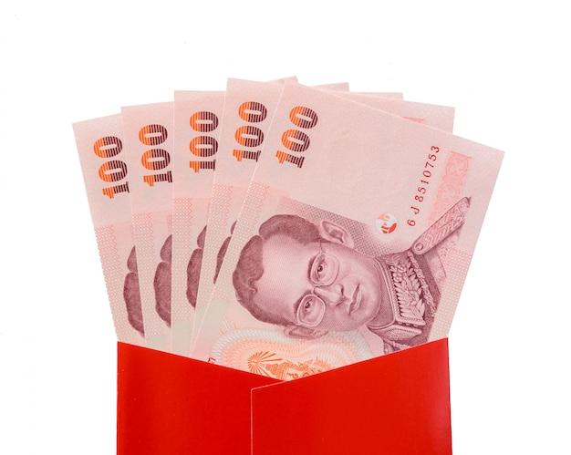 Tajlandzkiego bahta banknoty w czerwonej paczce dla chińskiego nowego roku prezenta na białym tle