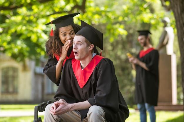 Tajniki. śliczna dziewczyna w akademickiej czapce szepcząca coś do ucha swojej przyjaciółce