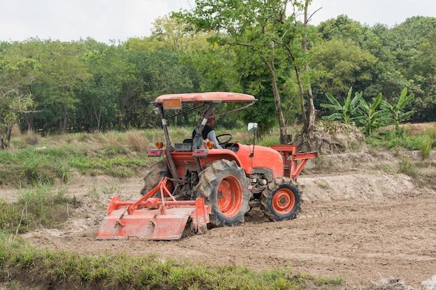 Tajscy rolnicy używają ciągnika do przygotowania gleby do uprawy ryżu.