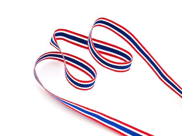 Tajska flaga wstążka z czerwonymi, niebieskimi i białymi paskami, symbole krajów azjatyckich na białym tle na białej powierzchni.