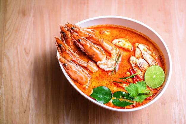 Tajska gorąca pikantna zupa krewetkowa w mleku kokosowym lub tom yum goong na drewnianym stole