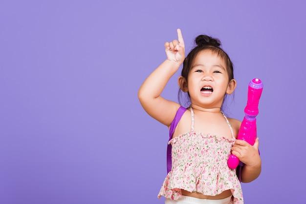 Tajska mała dziewczynka trzyma plastikowy pistolet na wodę, tajlandia święto songkran
