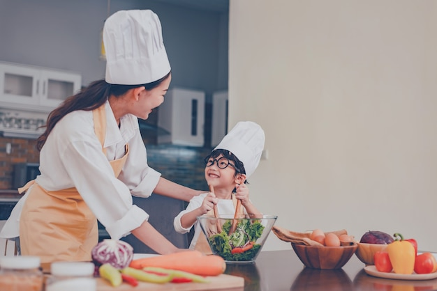 Tajska mama i dziecko wspólne gotowanie w domu. dystans społeczny i zostań w domu bądź bezpieczny. aktywność rodzinna wpływ covid-19 i powstrzymanie epidemii wirusa. zamknięcie i samodzielna kwarantanna w domu.