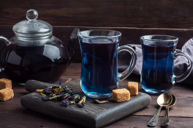Tajska niebieska herbata anchan z pączków klitoria ternate w szklanej filiżance, ciemna ściana.