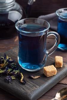Tajska niebieska herbata anchan z pączków klitoria ternate w szklanej filiżance, ciemny stół.