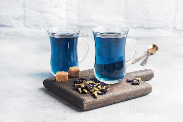 Tajska niebieska herbata anchan z pączków klitoria ternate w szklanym kubku, szary betonowy stół. skopiuj miejsce.