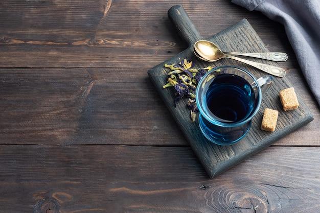Tajska niebieska herbata anchan z pąków klitoria ternate w szklanej filiżance, ciemne tło. skopiuj miejsce