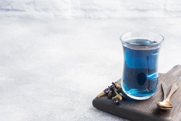 Tajska niebieska herbata anchan z pąków klitoria ternate w szklanej filiżance, szare tło betonowe. skopiuj miejsce.