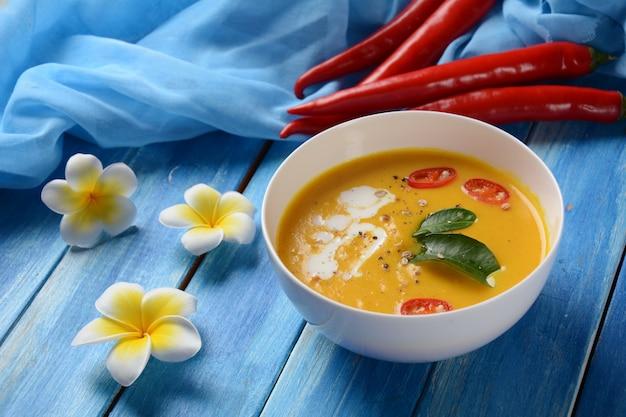 Tajska ostra zupa z dyni i mleka kokosowego z liśćmi limonki kafiru, czerwonym chilli i pudrem z korzeni galangalu.