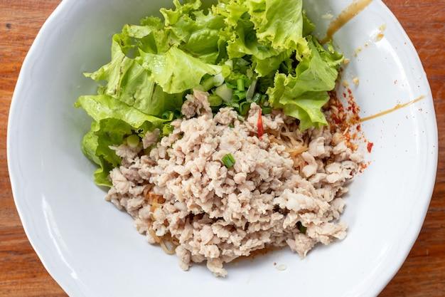 Tajska pikantna wieprzowina mielona z makaronem jajecznym podana na rustykalnym drewnianym stole.