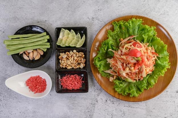 Tajska sałatka z papai w białym talerzu z fasolą szparagową, czosnkiem i białym sosem