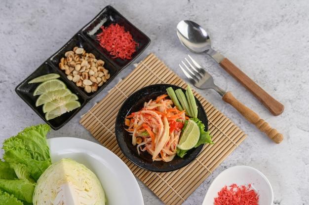 Tajska sałatka z papai w białym talerzu z lepkim ryżem i suszonymi krewetkami