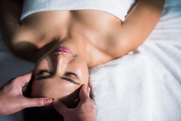 Tajski ajurwedyjski masaż twarzy na łóżku z piękną azjatką. zabieg przeciwstarzeniowy na twarz