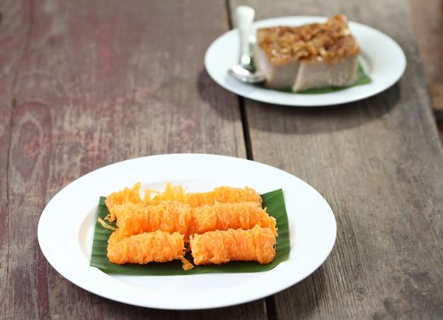 Tajski deser, kokosowe kwadraty z kremem i złote nici.