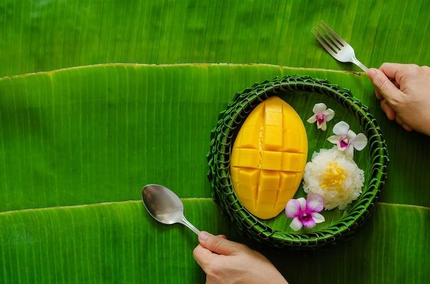 Tajski deser - lepki ryż z mango, który nakłada się na talerz z liści bananowca ręką trzymającą widelec i łyżkę.