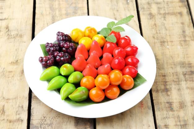 Tajski deser, możliwe do usunięcia imitacje owoców na białym talerzu.