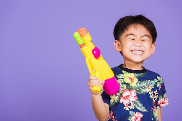 Tajski dzieciak zabawny pistolet na wodę z zabawkami i uśmiechnięty na dzień festiwalu songkran