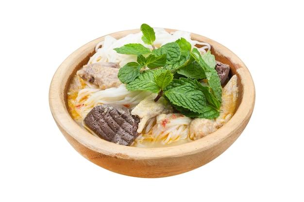 Tajski makaron ryżowy z makaronem wermiszelowym z kurczakiem curry i świeżą miętą na drewnianej misce