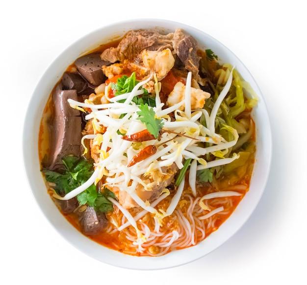 Tajski makaron ryżowy z pikantnym sosem wieprzowym. północny tajlandzki jedzenie robić ryżowy wermiszel lub ryżowy kluski w korzennym kumberlandzie z wieprzowiną lub mięsnym odgórnym widokiem odizolowywającym