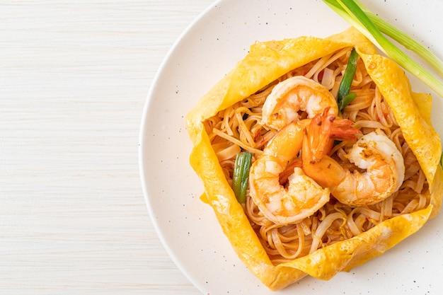 Tajski makaron smażony z krewetkami i owinięciem jajka (pad thai)