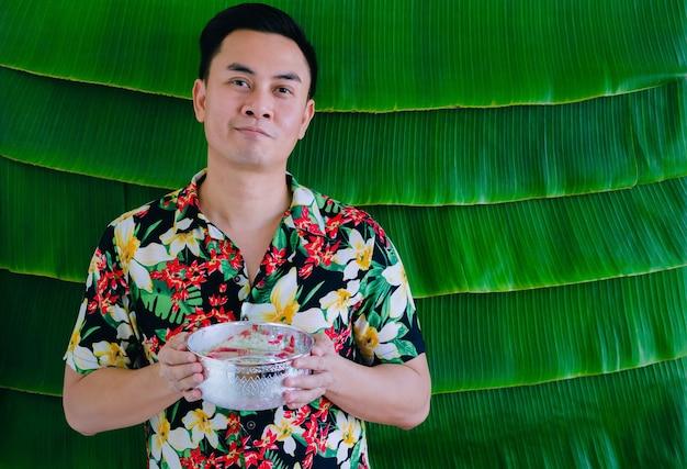 Tajski mężczyzna trzymający miskę z wodą, która ma kwiaty, aby błogosławić festiwal songkran na tle liści bananowca.