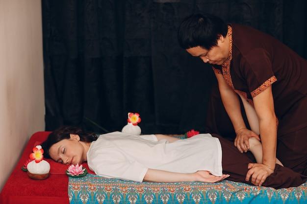 Tajski mężczyzna wykonujący klasyczny masaż tajski dla młodej kobiety w salonie piękności spa