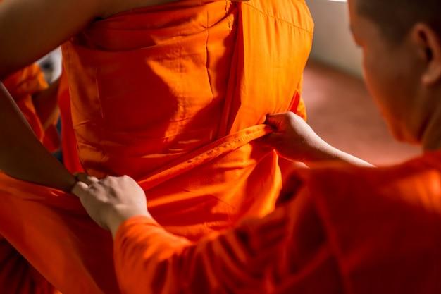 Tajski mnich pomaga w noszeniu pomarańczowej tkaniny mnicha, aby buddyjski mężczyzna zmienił sytuację na mnicha podczas ceremonii.