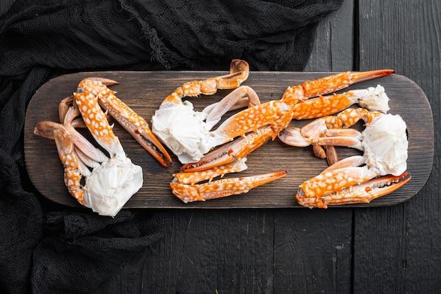 Tajski niebieski pływanie kraba zestaw gotowanych części mięsa, na tle czarnego drewnianego stołu, widok z góry płaski leżał