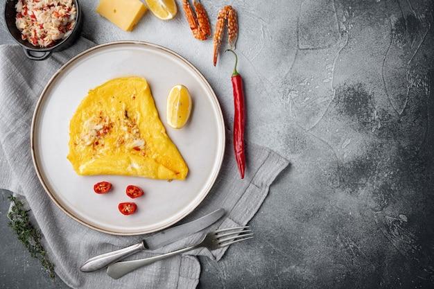 Tajski omlet azjatycki, świeże czerwone chilli, brązowe i białe mięso kraba, cytryna, ser cheddar i jajka, na talerzu, na szarym stole, widok z góry na płasko