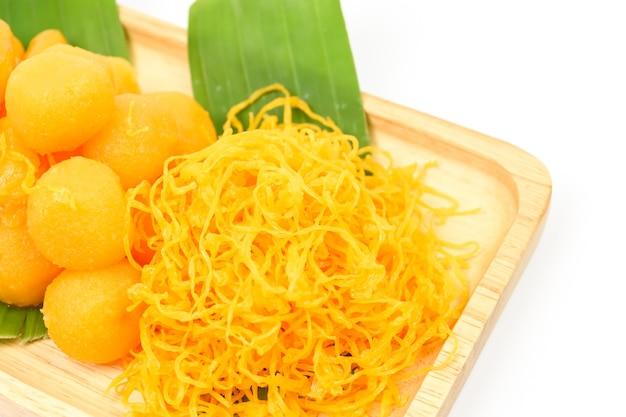 Tajski słodki deser (med khun, thong yod, foy thong) na drewnianej płycie z zielonym liściem bananowca na białym tle, tajskie tradycyjne desery