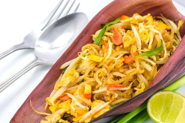 Tajski smażony makaron lub smażony w tajskim stylu mały makaron ryżowy (pad thai) na kwiat bananowca z widelcem i łyżką na białym tle, tajskie lokalne jedzenie