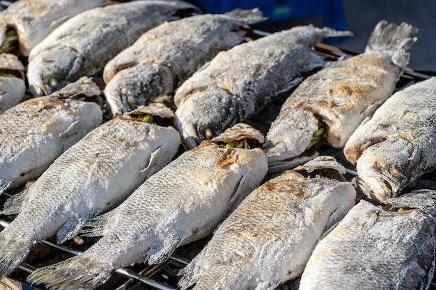 Tajski sprzedawca uliczny sprzedaje grillowane ryby na targu ulicznym na wyspie koh phangan w tajlandii. ścieśniać