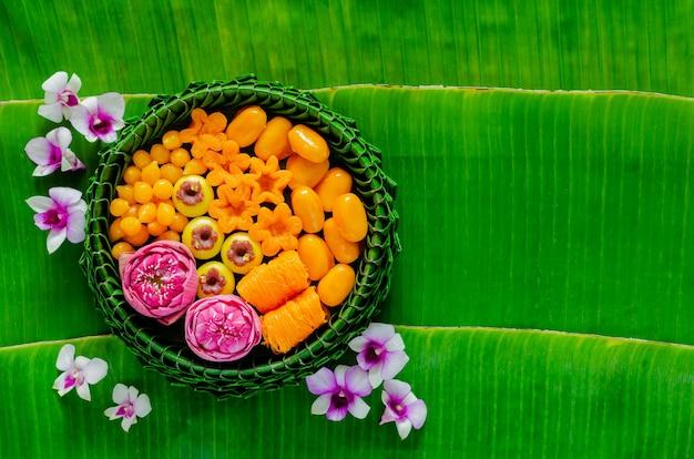 Tajskie desery ślubne na talerzu z liśćmi bananowca lub krathong udekorowane kwiatem lotosu na tradycyjną tajską ceremonię na liściu bananowca