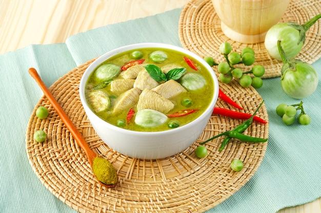 Tajskie jedzenie kurczak zielone curry na drewnianym talerzu, pokrojone filety z kurczaka, ćwiartowane bakłażany, bakłażan grochowy, liście bazylii, pieprz i mleko kokosowe. pasta z zielonego curry.