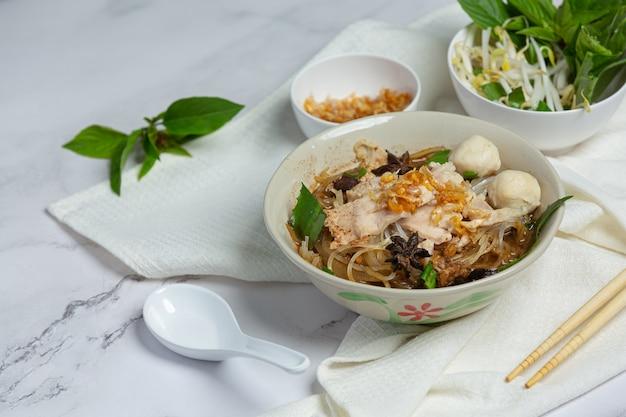 Tajskie jedzenie. makaron z wieprzowiną, klopsikiem i warzywami