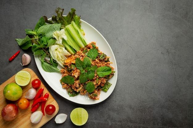 Tajskie jedzenie; pikantna mielona wieprzowina podawana z dodatkami