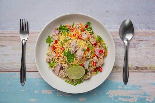 Tajskie jedzenie. pikantna sałatka z makaronem instant z mieloną wieprzowiną