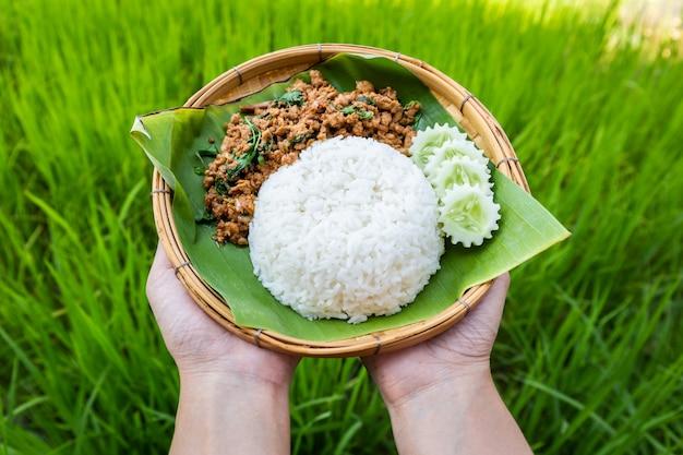 Tajskie jedzenie ryż zwieńczony smażonym wieprzowiną i bazylią ogórkiem w tradycyjnym naczyniu z bambusa
