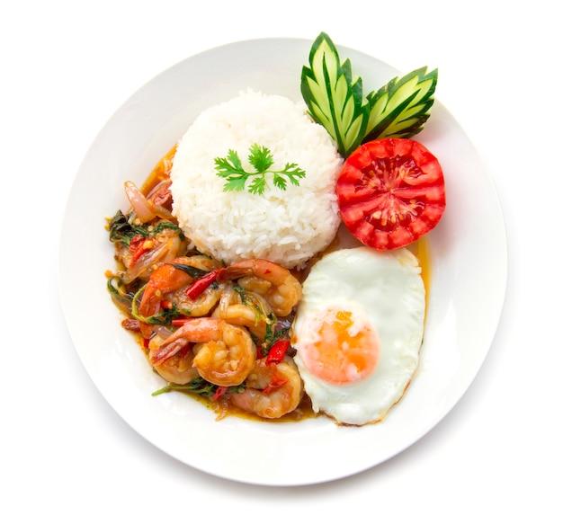 Tajskie jedzenie smażone krewetki pikantne i bazylia podawane z ryżem i jajkiem sadzonym i ogórkiem pomidorowym