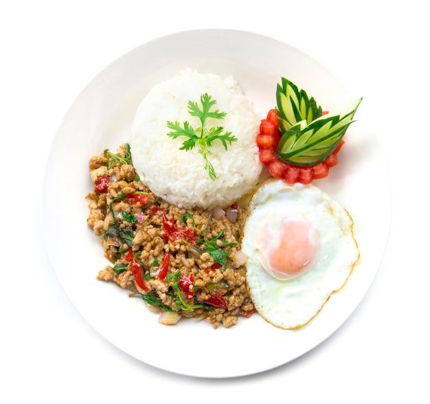Tajskie jedzenie smażone na ostro wieprzowe pikantne i bazylia podawane z ryżem i jajkiem sadzonym i ogórkiem pomidorowym