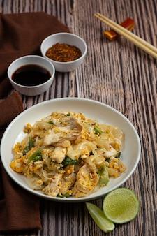 Tajskie jedzenie. smażony makaron z wieprzowiną w sosie sojowym i warzywach