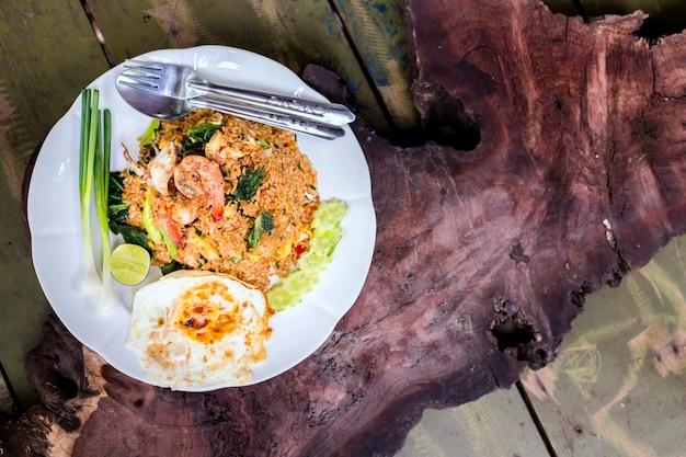 Tajskie jedzenie, smażony ryż owoce morza, krewetki, kalmary i smażone jajka na drewniane tła