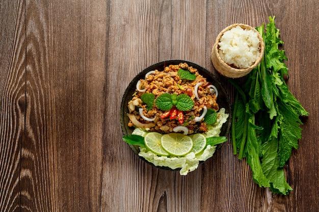 Tajskie jedzenie z pikantną mieloną wieprzowiną podajemy z dodatkami i lepkim ryżem