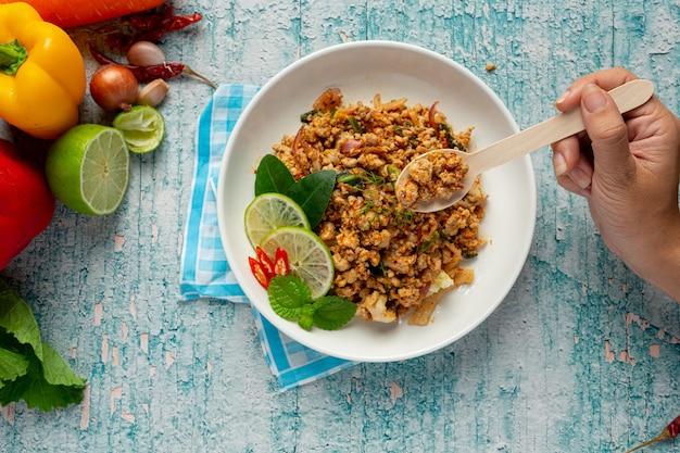 Tajskie jedzenie z pikantną mieloną wieprzowiną podawane z dodatkami