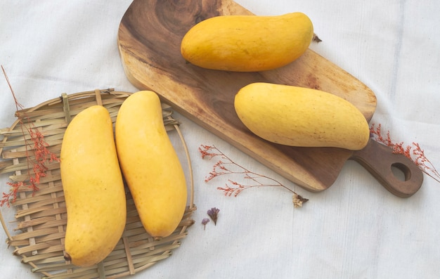 Tajskie mango umieszczone na drewnianej tacy obok suszonego kwiatu, na tle bawełnianej tkaniny