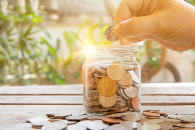 Tajskie monety w szklanej butelce i tle bokeh, biznesowa koncepcja oszczędzania pieniędzy