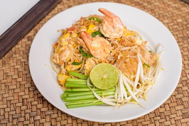 Tajskie tradycyjne potrawy pad tajski makaron z krewetkami w naczyniu na drewnianym stole