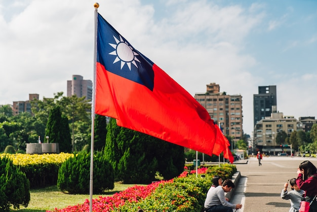 Tajwańska flaga narodowa macha na wietrze z turystami.