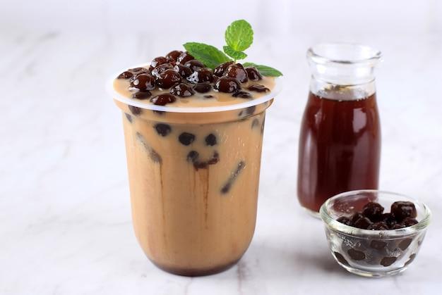 Tajwańska lodowa czekolada mleczna lub kawa z perłami boba tapioca na wierzchu z listkiem mięty jako dekoracją. przy drewnianym stole. czekoladowy napój boba